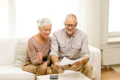 Senior couple with papers and calculator at home. Family, business, savings, age and people concept - smiling senior couple with papers and calculator at home Royalty Free Stock Photos
