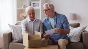 Senior couple with parcel and delivery note stock video footage