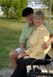 Senior couple on park bench. Portrait of a senior couple outdoors sitting on a park bench stock photography