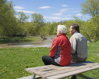 Senior couple on park picnic table. Senior couple sitting on picnic table looking at river on spring day Stock Photo
