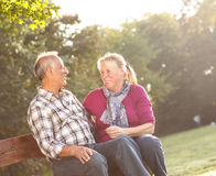 Senior couple in a park sitting on the bench Stock Photos