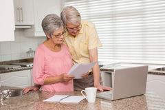 Senior couple paying their bills with laptop Stock Photography