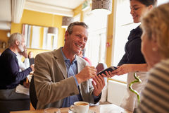 Senior couple paying waitress with card reader in restaurant Royalty Free Stock Images