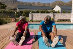 Senior couple performing stretching exercise in the backyard of home stock photos