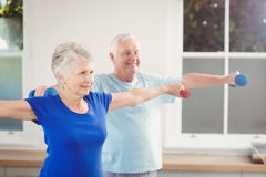 Senior couple performing stretching exercise. With dumbbells at home Stock Image