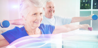 Senior couple performing stretching exercise. With dumbbells at home Stock Photography