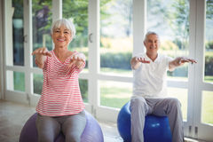Senior couple performing stretching exercise on fitness ball Royalty Free Stock Photos