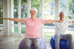 Senior couple performing stretching exercise on fitness ball Stock Photos