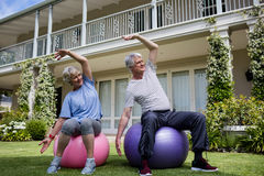 Senior couple performing stretching exercise on fitness ball. In lawn Stock Image