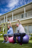 Senior couple performing stretching exercise on fitness ball. In lawn Royalty Free Stock Photos