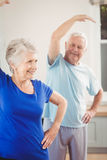 Senior couple performing stretching exercise. At home Stock Photos