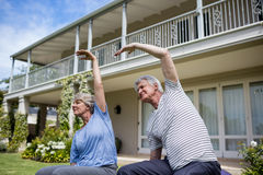Senior couple performing stretching exercise. In lawn Royalty Free Stock Photos