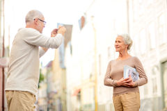 Senior couple photographing on city street Stock Images