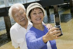 Senior couple photographing themselves by pier Royalty Free Stock Photography