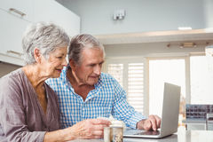 Senior couple with pills using laptop Royalty Free Stock Images