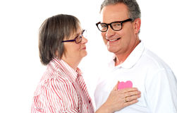 Senior couple with pink heart isolated on white Stock Image
