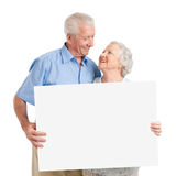 Senior couple with placard. Senior lovely couple holding together a white board isolated on white background Royalty Free Stock Images