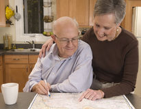 Senior couple planning a trip. Middle-aged or elderly couple studying a road atlas, planning a trip or vacation stock images