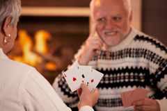 Senior couple playing cards. On winter night, cards handheld in focus Stock Photos