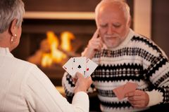 Senior couple playing cards. Focus on cards handheld by woman, three ace Royalty Free Stock Images