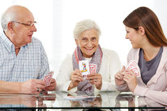 Senior couple playing cards. Happy senior couple playing cards with young woman Stock Images