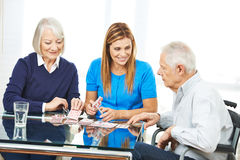 Senior couple playing cards with woman Royalty Free Stock Photos