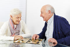 Senior couple playing checkers. Happy senior couple playing checkers together in a retirement home stock photography
