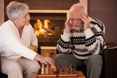 Senior couple playing chess at home. Smiling woman winning game, man thinking looking troubled Royalty Free Stock Photography