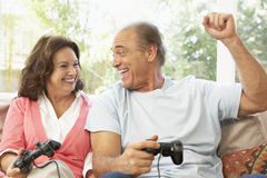 Senior Couple Playing Computer Game At Home. Man Celebrating Royalty Free Stock Photo
