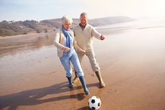 Senior Couple Playing Football On Winter Beach stock image