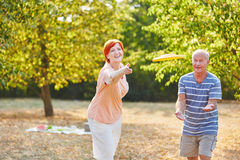 Senior couple playing frisbee and having fun Stock Photography
