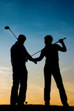 Senior couple playing Golf at sunset Stock Image