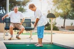 Senior couple playing miniature golf royalty free stock photos