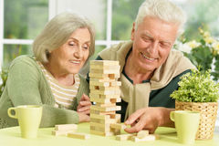 Senior couple playing in table game. Portrait of a happy senior couple playing in table game at home Stock Photos