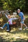 Senior couple playing with a wheelbarrow Royalty Free Stock Photos