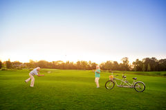 Senior couple plays badminton. Bike on the lawn. The score is equal. Sport in our life stock photo