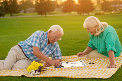 Senior couple plays checkers. Man and women on lawn. Make your move. Think and win royalty free stock image