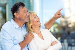 Senior couple pointing. Loving Senior Couple Outdoors Smiling Royalty Free Stock Image