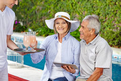 Senior couple at pool getting cocktails Royalty Free Stock Image