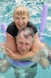 Senior couple pool piggyback. Close up shot of happy senior couple having fun doing a piggyback in a swimming pool Royalty Free Stock Photo