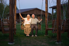Senior couple on porch swing. Man and women outdoor, evening Stock Photos