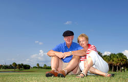 Senior couple portrait. Portrait of a senior couple outdoors sitting in the grass Stock Images