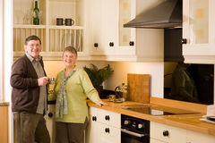 Senior couple portrait in modern designer kitchen Stock Photography