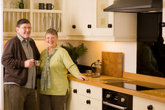 Senior couple portrait in modern designer kitchen Royalty Free Stock Image