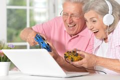 Senior couple portrait playing on laptop. At home Royalty Free Stock Photos