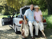 Senior couple posing beside car boot, man holding golf bag, smiling, portrait Royalty Free Stock Image