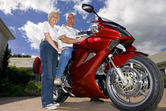 Senior couple posing on expensive motorcycle Stock Images