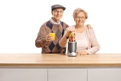 Senior couple posing with a fruit in a blender and a glass of healthy juice royalty free stock image