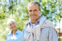 Senior Couple Posing in Nature. Portrait of contemporary senior man smiling at camera with wife in background, copy space royalty free stock photography