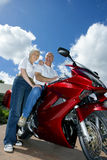 Senior couple posing beside red motorbike on driveway, smiling, side view, portrait (surface level, tilt) Royalty Free Stock Image